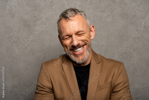 Fototapeta cheerful man with closed eyes laughing on grey