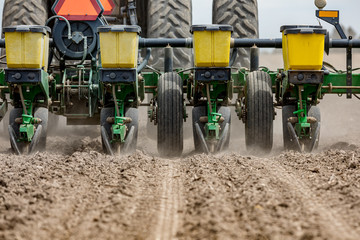 Closeup of tractor and planter in farm field planting corn or soybeans seed in dry, dusty soil during spring season