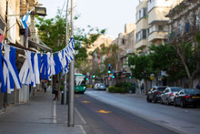 White And Blue Ribbons On Sky Background. Flags And Decorations For The Independence Day (Yom Haatzmaut) In An Israeli City.