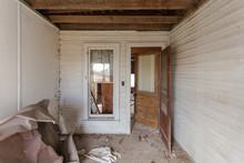 Wide Angle Shot Of Filthy Hallway In Abandoned Home With Open Door, Window And Wood Trim