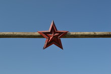 Low Angle View Of Red Star Shape Hanging On Wood Against Clear Blue Sky