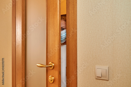 A little scared girl at medical protective face mask is looking through the door slit Wallpaper Mural