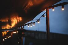 Illuminated Light Bulbs Hanging Against Sky At Night