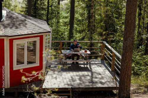 Fotografie, Tablou High angle view of middle aged man sitting at table on porch of country house su