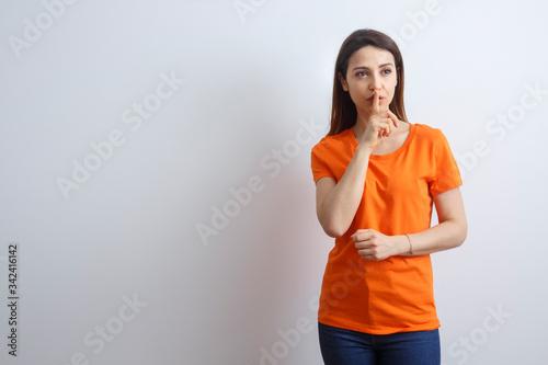 Giovane e bella ragazza con i capelli lisci, indossa una T-Shirt Arancione fa il Wallpaper Mural