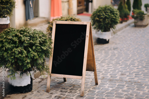 Photo An old black wooden billboard stands on a pavers stones