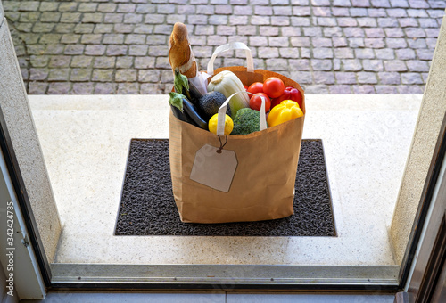 Fototapeta Contactless food delivery service concept. Paper bag with groceries delivered and left outside at entrance door. View from inside through open door.  Online shopping. Zero waste package obraz