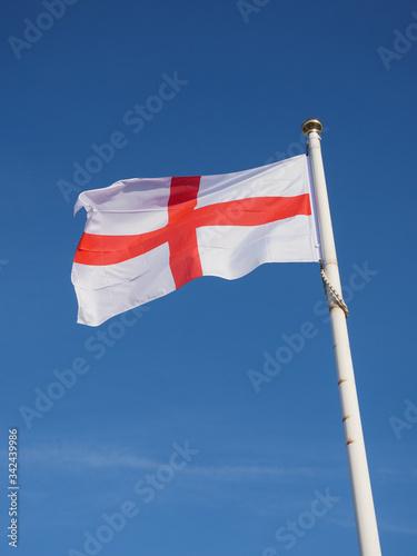Fényképezés English St George Cross flag aloft against a blue sky. England.