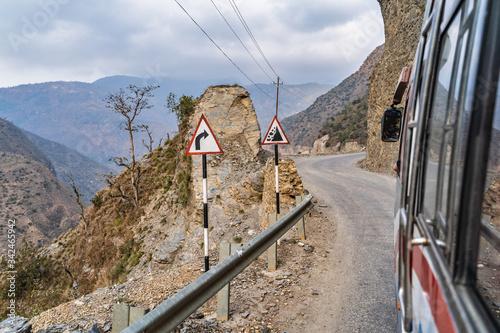 Fotografie, Obraz Road signs on a mountain road: turn right, carefully rockfall