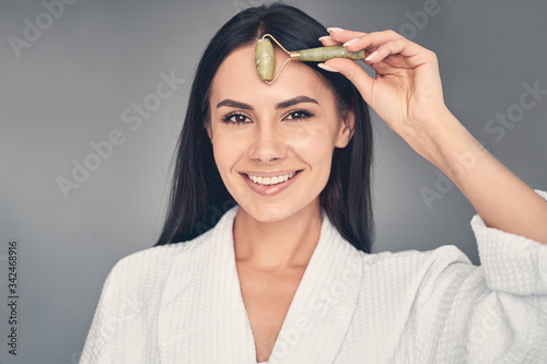 Pleased dark-haired young Caucasian woman looking forward Fototapet
