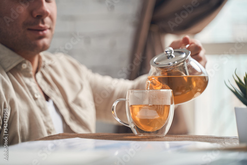Fototapeta Focused male holding a teapot infuser in his hand