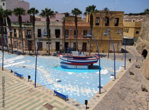 Square in the city of Melilla with fishing boat on the tiled blue floor. Spain.