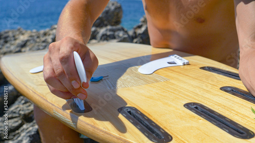 CLOSE UP: Unrecognizable surfer attaching white fins on bottom of his surfboard Canvas Print