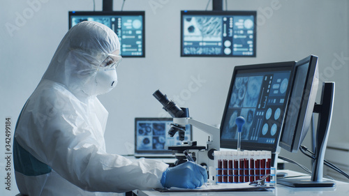 Photo Scientist in protection suit and masks working in research lab using laboratory equipment: microscopes, test tubes