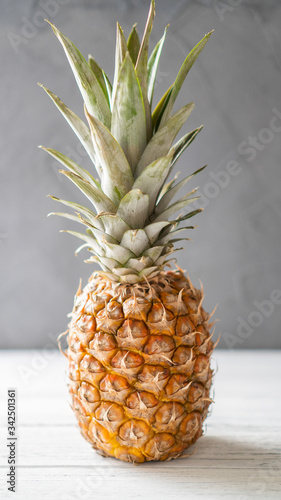 Fototapety, obrazy: Single ripe illuminated pineapple on a white wooden table and gray background. Juicy standalone ananas.