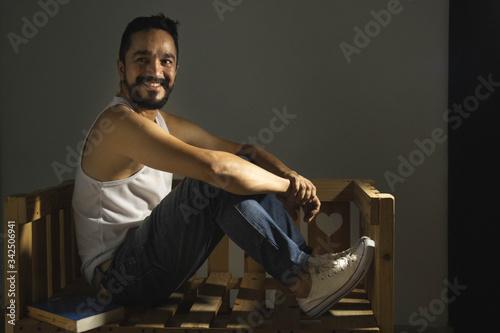 hombre con barba sentado en una banca sonriendo Canvas Print