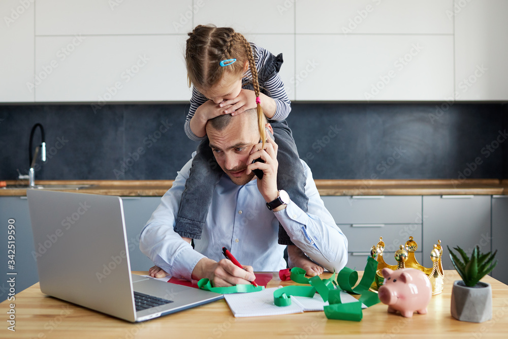 Fototapeta Father Working from home on laptop during quarantine. Little child girl make noise and distracts father from work on the kitchen office