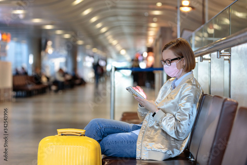 Fotomural Woman upset over flight cancellation, writes message to family, sitting in almost empty airport terminal due to coronavirus pandemic/Covid-19 outbreak travel restrictions, collapse