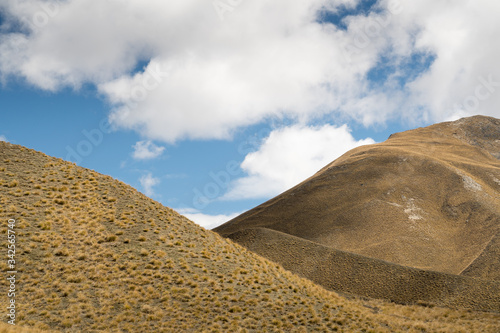 Abstact View of Tussock Grass Hills and Cloudy Blue Sky Wallpaper Mural