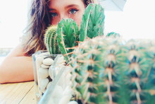 Close-up Portrait Of Young Woman By Cactus