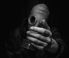 Close-up Of Man Holding Gas Mask Against Black Background