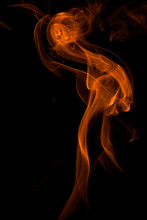 Close-up Of Orange Smoke Against Black Background