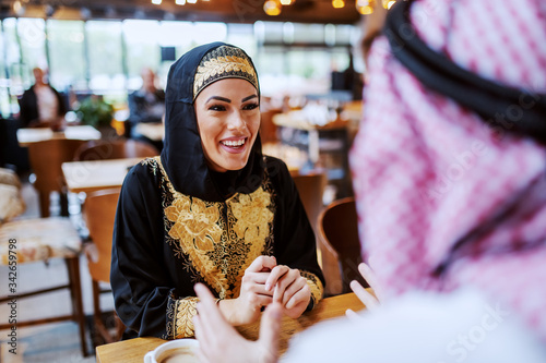 Attractive positive smiling arab woman sitting in cafe with her beloved husband and chatting Fototapet