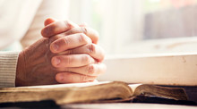 Hands Of A Man Praying Over A Bible - Represents Faith And Spirituality In Everyday Life