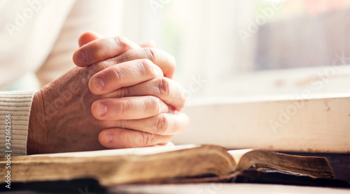 Photo Hands of a man praying over a Bible - represents faith and spirituality in every