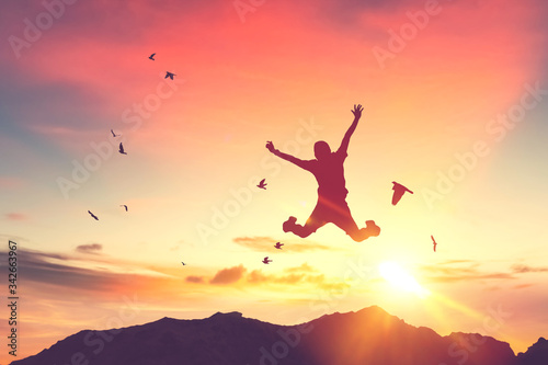 Fotografiet Silhouette man jump and birds fly on sunset sky and cloud texture abstract background