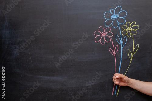 Fototapeta A man's hand holds flowers drawn on a chalkboard in his hand. obraz na płótnie