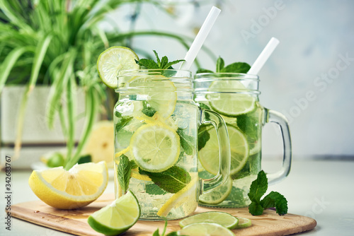 Fotografia Two glasses of homemade lemon, lime, and mint lemonade sit on the wooden dining table