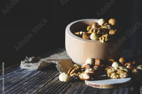 Assortment of nuts in a wooden bowl on the table Canvas Print