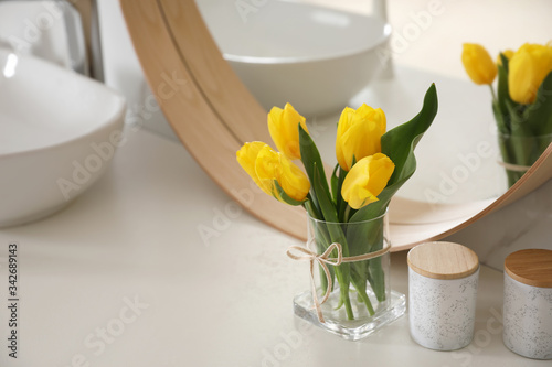 Beautiful yellow tulips near mirror on white table