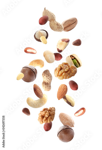 Fotomural Different nuts falling on white background