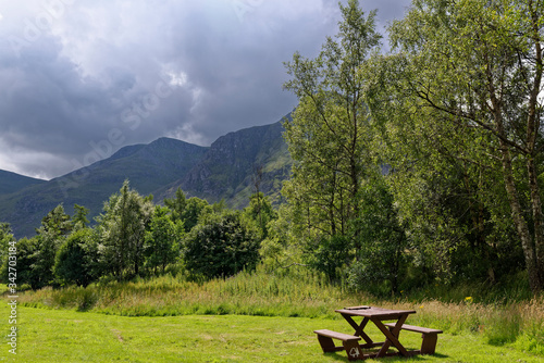 фотография A wooden bench and table set at the Glen Doll Picnic area at the head of Glen Clova in the Cairngorm National Park with rain clouds gathering above