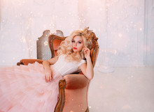 Young Beautiful Queen Woman Resting In Medieval Armchair. Beauty Face. New Year Garland Scenery Glare Sparks Bright. Backdrop White Classic Room Interior. Hairstyle Princess Girl Blonde Long Wavy Hair