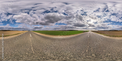 Fotografia Full spherical seamless hdri panorama 360 degrees angle view on no traffic asphalt road among fields in evening with cloudy sky