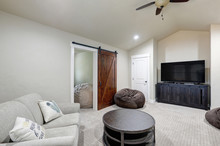 Bright Light Grey Living Room With TV, Stand And Round Table With Sofa And Barn Door.