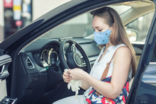 Young Woman Getting Out Of Her Car Wearing A Face Mask And Disposable Gloves. People Wearing Cloth Masks To Protect Themselves From Covid-19 Pandemic.