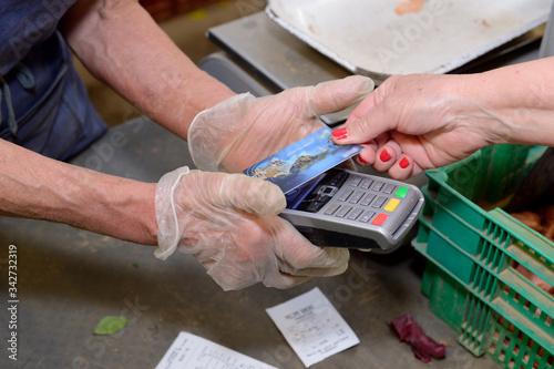 Obraz Coronavirus, gestes barrières. Paiement par carte bancaire sans contact sur un marché fermier - fototapety do salonu