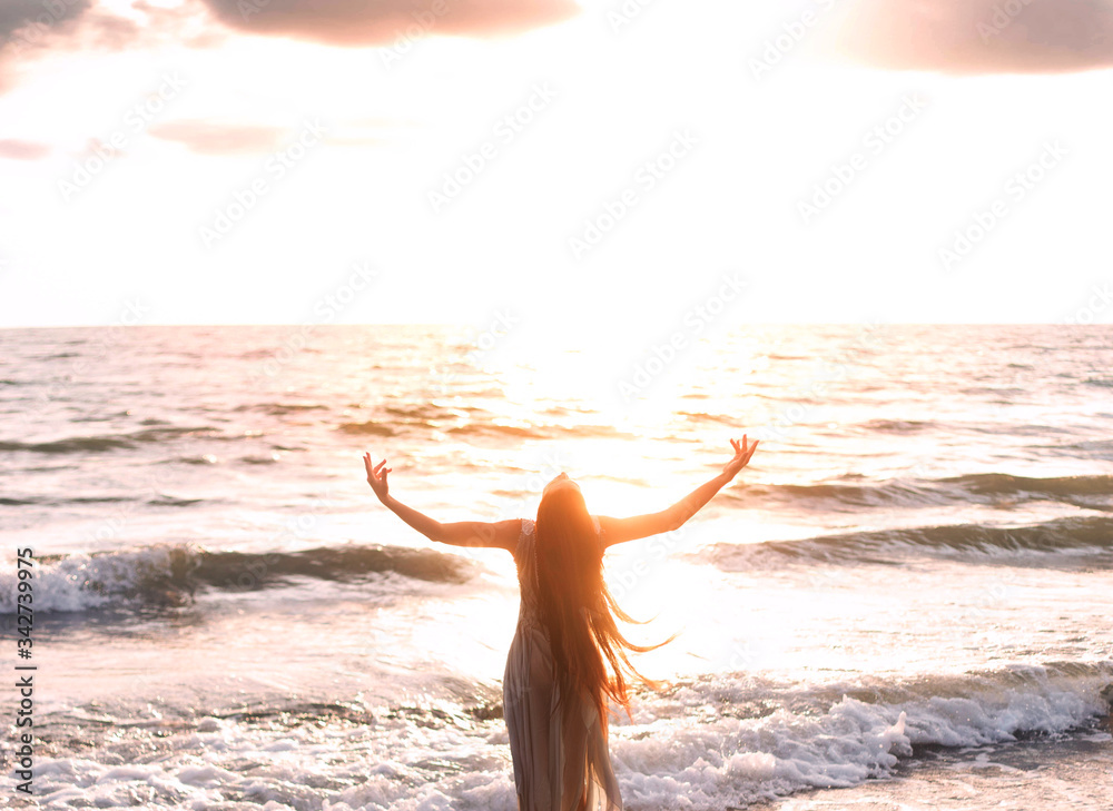 Fototapeta happy woman stands seashore turned away hand raised to heaven sky sun light. Lady girl enjoy sunny sunset sea waves. Concept hope divine pray freedom. Brunette long hair fluttering fly wind. Georgia