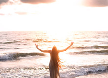 Happy Woman Stands Seashore Turned Away Hand Raised To Heaven Sky Sun Light. Lady Girl Enjoy Sunny Sunset Sea Waves. Concept Hope Divine Pray Freedom. Brunette Long Hair Fluttering Fly Wind. Georgia