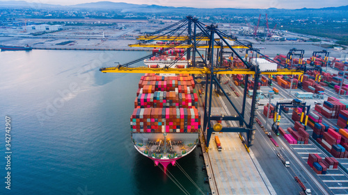 crane loanding cargo container to container ship in the international terminal yard port  concept freight shipping by ship at sunrise Fototapet