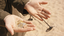 Close Up, Hands With The Coins. Person Searching Sandy Beach With Metal Detector. Treasure Hunt