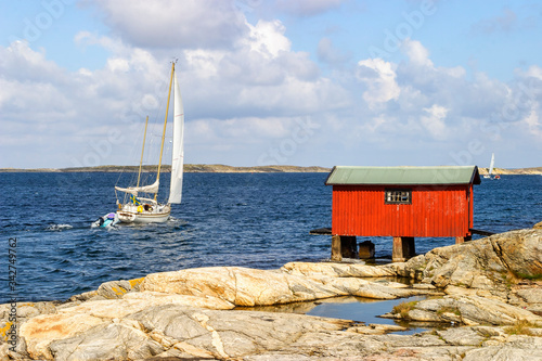 Fotografiet Sailboat at sea with a red boathouse on the rocks in the archipelago