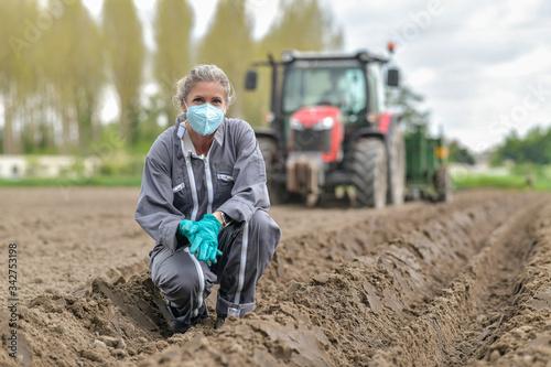 Obraz Female farmer  analyses the soil before planting and wearing a protective mask against coronavirus - fototapety do salonu