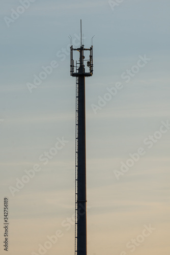 Photo Telecommunication tower with cellular network antenna against blue sky as backgr