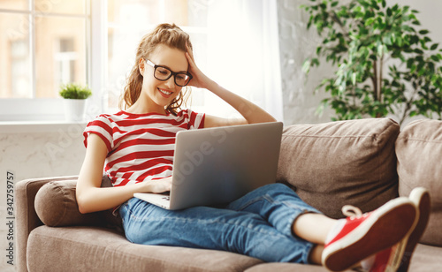 Fototapeta Joyful relaxed woman using laptop with interest at home. obraz