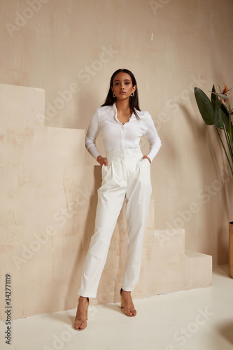 Photo Beautiful sexy brunette woman tanned skin face cosmetic makeup wear white suit pants for date walk office fashion clothes style collection interior room  sand color safari summer casual